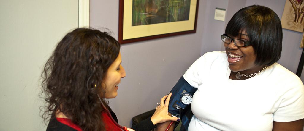 Nurse practitioner taking smiling client's blood pressure.